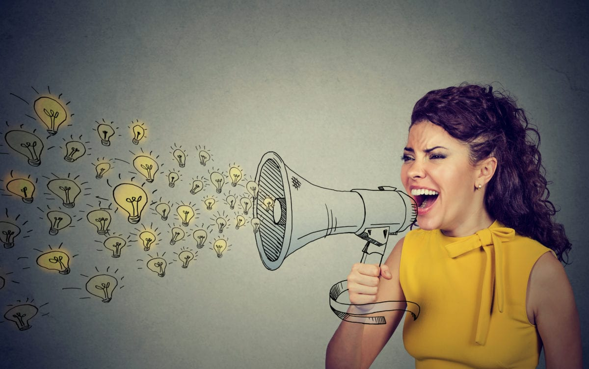 Business woman screaming out her ideas loud in megaphone